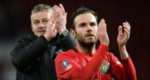 Manchester United manager Ole Gunnar Solskjær  and goalscorer Juan Mata applaud fans after the  FA Cup third-round replay victory over Wolves at Old Trafford. Photograph: Peter Powell/EPA