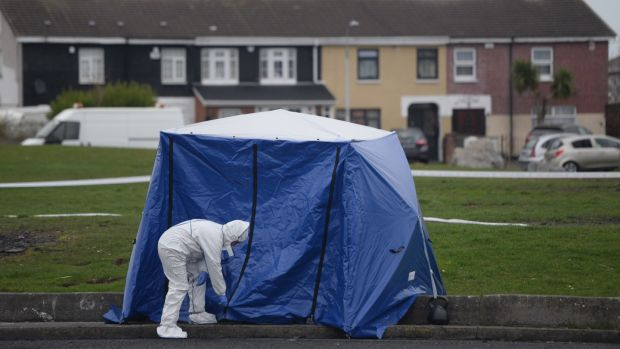 Gardaí at the scene in Coolock on Tuesday morning where a bag containing human limbs was found. Photograph: Dara Mac Dónaill