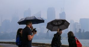 Tourists are seen taking pictures of Sydney Harbour in the rain on January 17th,  in Sydney. Photograph: Jenny Evans/Getty Images