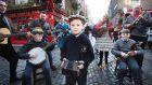 From left, Conor Mullin (12), Robert Mullin (7) and John Mullin (13) playing in Temple Bar while artists from Tradfest, the traditional music festival, perform an impromptu session. Tradfest runs from Januar 22nd-26th. Photograph: Leon Farrell/Photocall Ireland
