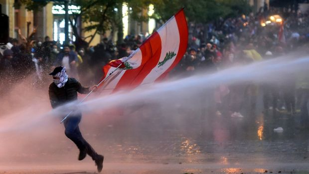 Lebanese riot police spray water cannons to disperse anti-government protestors during a protest outside of the Lebanese parliament in Beirut on Saturday. Photograph: Wael Hamzeh/EPA