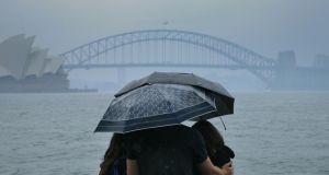 Tourists are seen looking at the Sydney Harbour Bridge in the rain on January 17th. Photograph: Jenny Evans/Getty