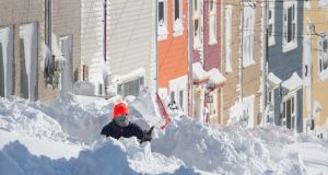 A resident digs out his walkway in St John's in Newfoundland on Saturday. Photograph: Andrew Vaughan/Canadian Press via AP