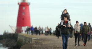 LIGHTHOUSE FAMILY: Fergal Carroll and his son Kyle out walking along the Great South Wall in Dublin. Photograph: Damien Eagers/The Irish Times