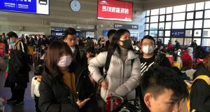 Passengers wearing masks wait to board trains at the Beijing West Railway Station, in Beijing, China, on Monday. Photograph: Reuters