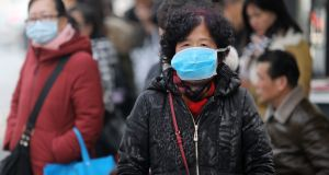 Chinese residents wear masks while waiting at a bus station near the closed Huanan Seafood Wholesale Market, which has been linked to cases of a new strain of Coronavirus. Photograph: EPA