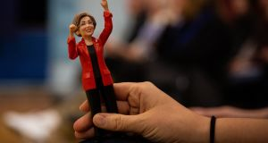 A supporter holds a figurine of Sen. Elizabeth Warren (D-Mass.), at her campaign event at Rye Junior High School in Rye, N.H., Dec. 7, 2019. (Elizabeth Frantz/The New York Times)