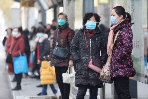 WIDESPREAD PRECAUTIONS: Commuters wear masks while waiting at a bus station near the closed Huanan Seafood Wholesale Market, which has been linked to cases of a new strain of Coronavirus identified as the cause of the current pneumonia outbreak, in Wuhan, Hubei province, China. Photograph: EPA
