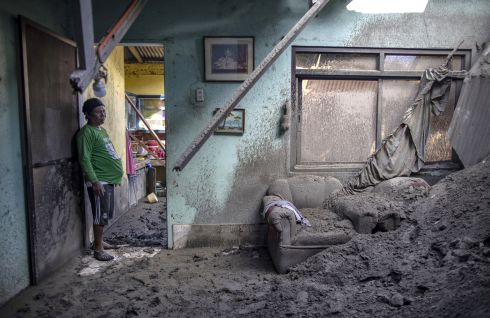 DUST TO DUST: Alex Polopot stands in the living room of his house, where the roof had collapsed due to heavy volcanic ash from the eruption of Taal Volcano, in the village of Buso Buso, Laurel, Batangas province, Philippines. Photograph: Ezra Acayan/Getty