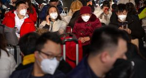Travellers wear face masks as they sit in a waiting room at the Beijing West Railway Station in Beijing. Photograph: Mark Schiefelbein/AP Photo
