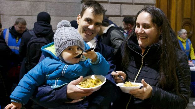 Cristina Moczek, her husband Constantin Neacsu and their son Emmanuel (2) with food from Feed Our Homeless at College Green, Dublin. Photograph: Damien Eagers