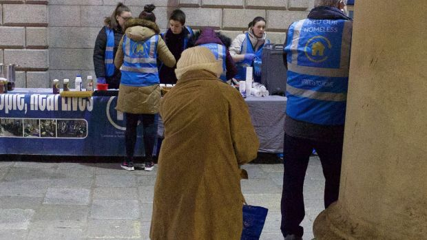 An elderly woman watches as the Feed Our Homeless charity provides help at College Green in Dublin. Photograph: Damien Eagers