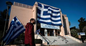 A man walks past a big national Greek flag hanging on the facade of the municipal theatre of Mytilene in the island of Lesbos on January 22nd, 2020. Photograph: Aris Messinis/AFP via Getty Images
