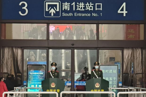 Guards wearing face masks stand at Hankou railway station in Wuhan, China on Wednesday. Photograph: Xiaolu Chu/Getty