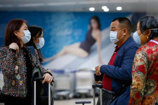 Passengers wearing face masks who arrived from Guangzhou, China gather at the Ninoy Aquino International Airport in Manila, Philippines on Wednesday. At least nine people have died and more than 400 people are confirmed infected by the coronavirus which was first detected in Wuhan, China. Photograph: Mark R Cristino/EPA.