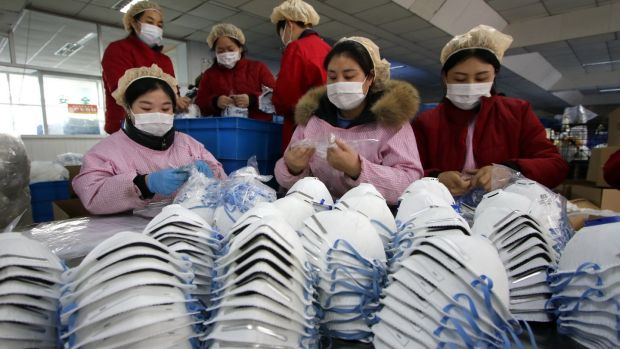 Workers manufacture protective face masks in a factory, as face mask stocks run low amid the outbreak of coronavirus, in Handan, Hebei Province, China. Photograph: EPA
