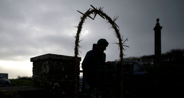 A man pases under a garland of reeds as he enters the holy well of St Brigid  in Liscannor. Photograph: Clodagh Kilcoyne/Reuters.