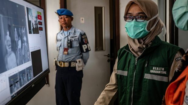 A health official monitors as passengers from an international flight have their temperature checked as they pass a thermal scanner monitor upon arrival at the Adisucipto International Airport in Yogyakarta, Indonesia. Photograph: Ulet Ifansasti/Getty Images