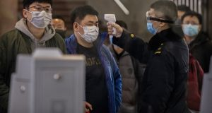 A  passenger who  arrived on the last bullet train from Wuhan to Beijing is checked for a fever by a health worker on Thursday. Photograph: Kevin Frayer/Getty Images