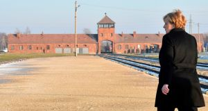 German Chancellor Angela Merkel walks in front of the main railway entrance to Birkenau as she visits the former German Nazi death camp Auschwitz-Birkenau in Oswiecim, Poland on December 6, 2019. - Merkel is on her first visit to the Auschwitz former German death camp.  (Photo by JOHN MACDOUGALL/AFP via Getty Images)