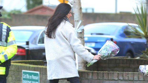 A woman leaves flowers outside the house in Parson's Court in Newcastle in which the bodies of three children were found. Photograph: Collins