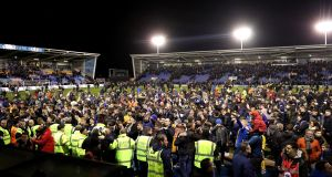 Shrewsbury fans invade the pitch after their draw with Liverpool. Photograph: