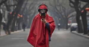 A Chinese man wears a protective mask, goggles and coat as he stands in a nearly empty street during the Chinese New Year holiday on Sunday in Beijing, China. Photograph: Kevin Frayer/Getty
