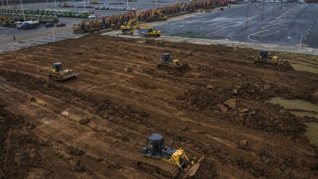 Bulldozers are used at a construction site of a field hospital in Wuhan, Hubei province, China. Wuhan Leishenshan hospital will be completed on February 5th, with a capacity of 1,300 beds for coronavirus patients, according to the government. Photograph: Getty