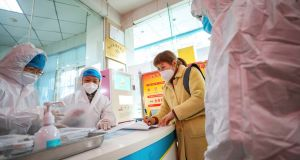 Medical workers in protective gear talk with a woman suspected of being ill with  the coronavirus at a health station in Wuhan, central China's Hubei Province, on Monday.  Photograph: Chinatopix via AP