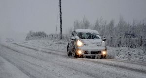 A car drives along a snow covered road near Knock in Co Mayo. Photograph: Paul Mealey