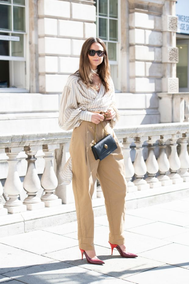 Florrie Thomas wears a Kurt Geiger bag, Victoria Beckham shoes, Rag and Bone sunglasses, Flow belt, trousers and shirt. Photograph: Kirstin Sinclair/Getty Images for Kurt Geiger.