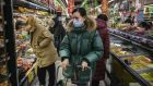 A  woman wears a protective mask and sunglasses in a supermarket  in Beijing. Photograph: Kevin Frayer/Getty Images