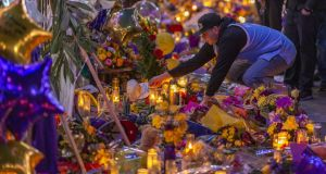 A man places a hat at a makeshift memorial near Staples Center in remembrance of former NBA great Kobe Bryant. Photograph:  David McNew/Getty Images