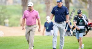Graeme McDowell  and Phil Mickelson  walk along the 14th hole during the second round of the  Saudi International at Royal Greens Golf and Country Club in King Abdullah Economic City, Saudi Arabia. Photograph: Ross Kinnaird/Getty Images