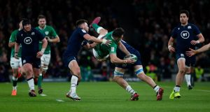 Ireland's Jacob Stockdale us upended by Scotland's Ali Price and Nick Haining. Photo: Tom Honan/The Irish Times