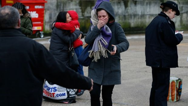A woman reacts as police officers interview people near to the scene where a man was shot and killed by armed police in London. Photograph: Hollie Adams/Getty Images
