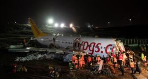 Emergency services workers evacute passengers after a Pegasus Airlines plane skidded off the Sabiha Gokcen airport runway in Istanbul, Turkey, on Friday. Photograph: EPA