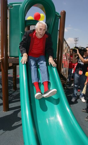 Kirk Douglas on a slide at the opening of teh 400th Anne and Kirk Douglas Playground at Lillian Street Elementary School, Los Angeles, California, in May 2008. Photograph: Valerie Macon/AFP/Getty Images