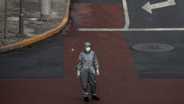 A Chinese woman wears a protective suit and mask as she waits to cross the intersection of a nearly empty street on February 8th in Beijing, China. Photograph: Kevin Frayer/Getty