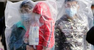 Passengers wearing masks and covered with plastic bags walk outside the Shanghai railway station in  China. Photograph:  Aly Song/Reuters