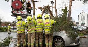 Members of Ennis fire brigade free a car from under a tree felled by Storm Ciara at Friars Walk, Ennis on Sunday. Photograph: Eamon Ward