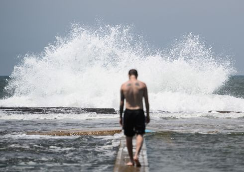 WIND AND WAVES: A man gets set for swimming as waves crash against North Narabeen Rockpool at Sydney's Northern Beaches, New South Wales, Australia. Waterlogged parts of the state are suffering their worst floods in years, with heavy rains and damaging winds forecast again, bringing some relief after the devastating bushfires of recent months. Photograph: James Gourley/EPA