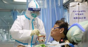 A nurse in a protective suit feeds a novel coronavirus patient inside an isolated ward at Zhongnan Hospital of Wuhan University. Photograph: China Daily via Reuters