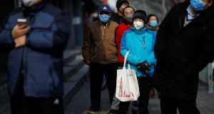 Customers wearing face masks queue for food outside a store in Beijing on Wednesday. Photograph: Carlos Garcia Rawlins/Reuters