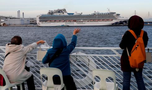 Tourists on a sightseeing cruise ship wave to passengers of the cruise ship Diamond Princess, which is anchored at Daikoku Pier Cruise Terminal in Yokohama, south of Tokyo, Japan February 12, 2020. Photograph : Kim Kyung-hoon / Reuters