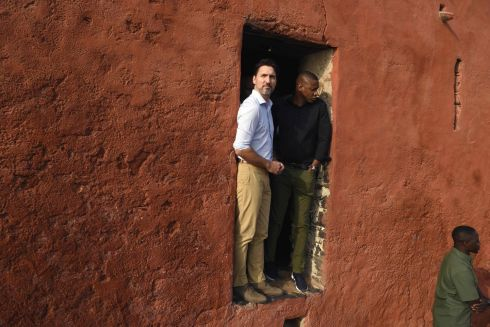 "Canadian Prime Minister Justin Trudeau (L) talks with Masai Ujiri (C), President of the Toronto Raptors, at the ""Door of the Journey of No Return"" at the Goree Slave House, during his visit to Senegal, on Goree Island off the coast of Dakar on February 12, 2020. Photograph : Seyllou / AFP"