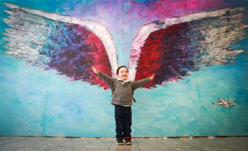 Chris Jenkins, aged 2 poses in front of LA artist Colette Miller's 'Wings', one of the world's most photographed pieces of street art, which has been recreated at Heathrow as part of the airport's bid to become the most 'Instagrammed' airport in the world. Photograph: Matt Alexander/PA Wire
