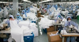 Workers producing protective clothing at a factory which previously produced suits and sportswear and switched production for the fight against coronavirus in Wuxi in China's eastern Jiangsu province. Photograph: Getty Images
