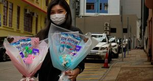 Flower shop owner Iris Leung wears her protective face mask as she delivers flowers with masks to customers on Valentine's Day in Hong Kong. Photograph: AP