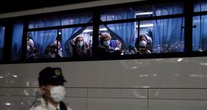 US citizens wave from a bus as they leave the Diamond Princess cruise ship  in Yokohama on Sunday night. Photograph:  Franck Robichon/EPA